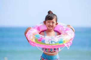 海で浮き輪を持って笑う女の子の写真素材 [FYI04018656]