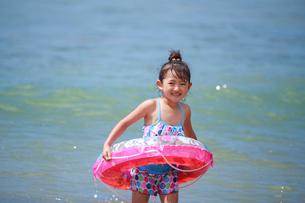 海で浮き輪を持って遊ぶ女の子の写真素材 [FYI04018657]