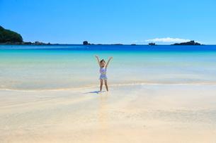 浜辺で両手を上げる女の子の写真素材 [FYI04018661]