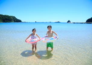 海で浮き輪を持って笑う兄妹の写真素材 [FYI04018663]