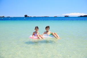 海で浮き輪に乗って浮かぶ兄妹の写真素材 [FYI04018665]