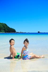 波打ち際に座る水着を着た兄妹の写真素材 [FYI04018666]