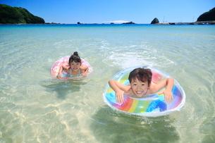 海で浮き輪を使って泳ぐ兄妹の写真素材 [FYI04018667]