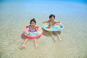 波打ち際で浮き輪を持って遊ぶ兄妹の写真素材 [FYI04018668]