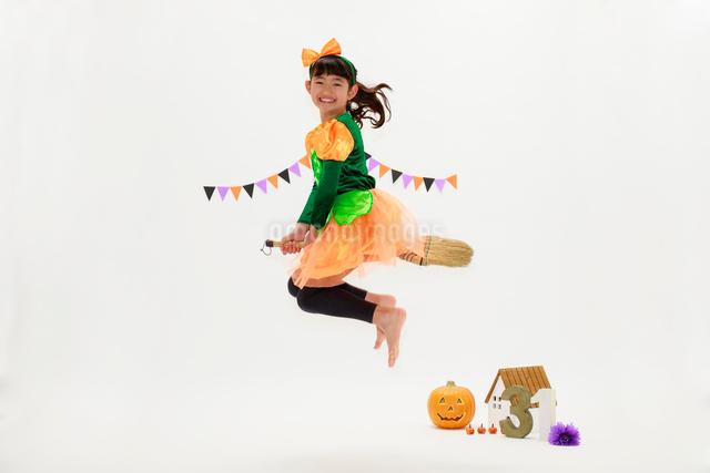 ハロウィンの仮装をしてジャンプする少女の写真素材 [FYI04018696]