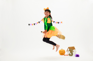 ハロウィンの仮装をしてジャンプする少女の写真素材 [FYI04018697]