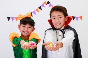 ハロウィンの仮装をしてお菓子を持った少年と少女の写真素材 [FYI04018705]