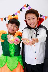 ハロウィンの仮装をしてお菓子を持った少年と少女の写真素材 [FYI04018708]