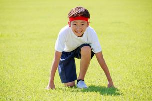 芝生の上でスタートを待つ少年の写真素材 [FYI04018772]