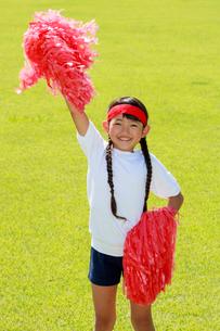 芝生の上で応援する少女の写真素材 [FYI04018778]
