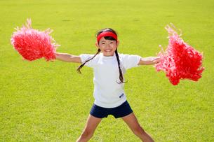 芝生の上で応援する少女の写真素材 [FYI04018781]