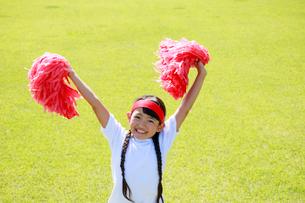 芝生の上で応援する少女の写真素材 [FYI04018783]