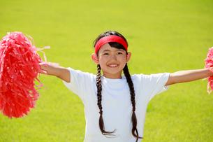 芝生の上で応援する少女の写真素材 [FYI04018784]