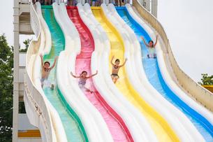ウォータースライダーをすべる子供たちの写真素材 [FYI04018931]