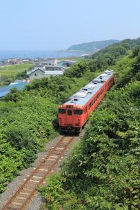 鯵ヶ沢を走行中の五能線普通列車の写真素材 [FYI04019309]