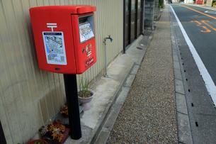 郵便ポストに貼られた津波緊急避難場所マップと道路の写真素材 [FYI04021801]