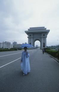 平壌市街の凱旋門前を歩く民族衣装を纏った女性の写真素材 [FYI04027689]