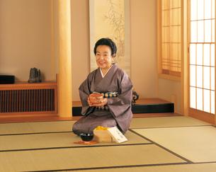 茶碗を見る60才代の女性の写真素材 [FYI04028368]