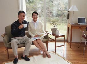 ソファでくつろぐ熟年夫婦の写真素材 [FYI04028656]