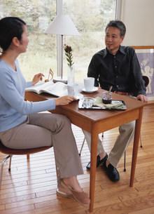 デスクでコーヒーを飲む熟年夫婦の写真素材 [FYI04028657]