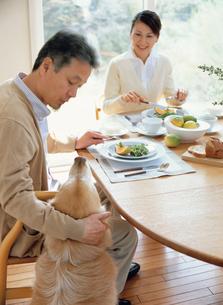 食事中の熟年夫婦と犬の写真素材 [FYI04028679]