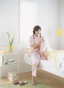 パジャマ姿でメールをする女性の写真素材 [FYI04028755]