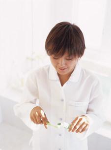 歯ブラシに歯磨き粉をつける女性の写真素材 [FYI04028831]