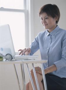 パソコンに向かう女性の写真素材 [FYI04028835]