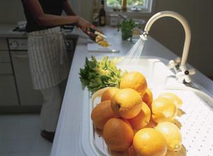 オレンジとキッチンに立つ女性の写真素材 [FYI04028836]