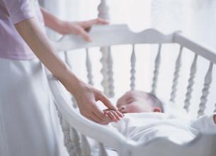 揺りかごの中の赤ちゃんと母の手の写真素材 [FYI04028850]