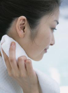タオルで首元を押さえる女性の写真素材 [FYI04028892]