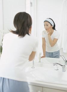 洗面所の鏡に向かう女性の写真素材 [FYI04028895]