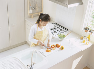 キッチンで料理する女性の写真素材 [FYI04028901]