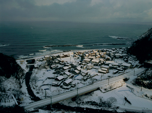雪景色 朝陽に染まる集落の写真素材 [FYI04034898]
