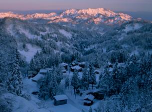 雪景色 朝焼けの黒姫山と集落の写真素材 [FYI04034901]