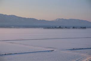 雪に覆われた田んぼと山の写真素材 [FYI04035161]