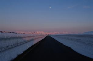 除雪された一本道と夕日を浴びる山の峰の写真素材 [FYI04035220]