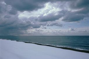 雲がたれ込める日本海と雪の浜辺の写真素材 [FYI04035256]