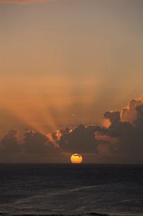 日本海に沈む夕日と雲間からの太陽光線の写真素材 [FYI04035263]