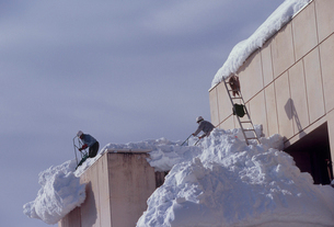 屋根の雪おろし作業風景の写真素材 [FYI04035660]