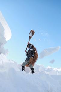 屋根の雪下ろし作業をする男性の写真素材 [FYI04035725]
