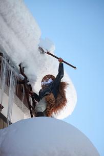 屋根の雪下ろし作業をする男性の写真素材 [FYI04035728]