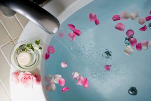 花びらを浮べた浴槽に置かれた蝋燭と花の写真素材 [FYI04037154]