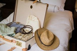 ベッドに置かれた旅行鞄と衣服と帽子の写真素材 [FYI04037163]