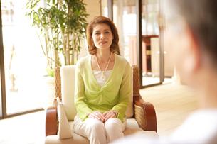 ロビーのソファに座る50代女性の写真素材 [FYI04037267]