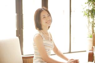 ロビーのソファに座る20代女性の写真素材 [FYI04037269]
