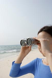 海で双眼鏡を覗く女性の写真素材 [FYI04037362]