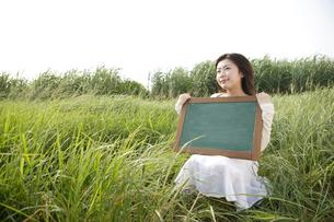 メッセージボードを持っている女性の写真素材 [FYI04037374]