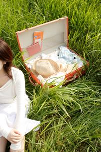 草原の中のトランクを持った女性の写真素材 [FYI04037375]