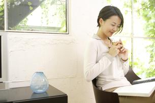 室内で雑誌を読む女性の写真素材 [FYI04037492]